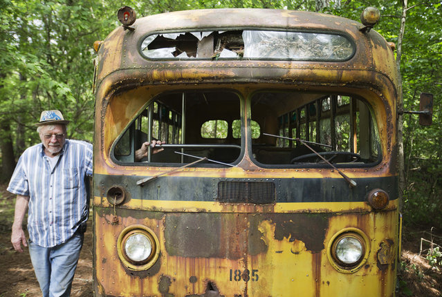Owner Walter Dean Lewis walks past a 1950s school bus as it sits at Old Car City, the world's largest known classic car junkyard Thursday, July 16, 2015, in White, Ga. (Photo by David Goldman/AP Photo)