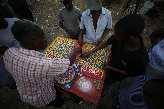 Residents awaiting the start of the weekly bullfights, where pairs of bulls go head-to-head, bet on a roulette-like game in the village of Barriere Jeudi, outside Leogane, Haiti, Saturday, October 5, 2019. The political turmoil is hitting cities and towns outside the capital of Port-au-Prince especially hard, forcing non-government organizations to suspend aid as barricades ranging from large rocks to burning tires cut off the flow of goods between the city and the countryside, further deepening poverty in places like Leogane. (Photo by Rebecca Blackwell/AP Photo)
