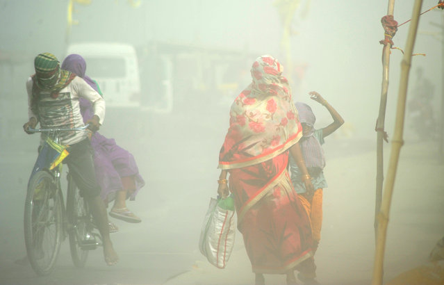 Indian pedestrians and cyclists travel through a dust storm at the Sangam, the confluence of the rivers Ganges, Yamuna and mythical Saraswati in Allahabad on May 5, 2017. (Photo by Sanjay Kanojia/AFP Photo)