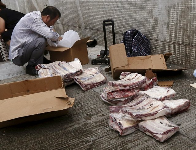 A man unpacks frozen beef ribs from the U.S. on a back street at an industrial area in Hong Kong, before they are hand carried and smuggled across the border into mainland China, July 13, 2015. (Photo by Bobby Yip/Reuters)