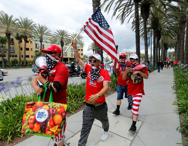 Supporters of U.S. Republican presidential candidate Donald Trump march down a street waving the U.S. flag after Trump spoke at a campaign event in Anaheim, California, U.S., May 25, 2016. (Photo by Mike Blake/Reuters)