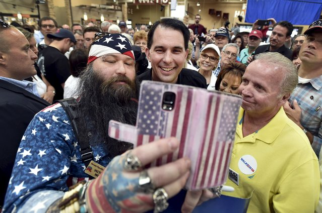 Republican presidential candidate and Wisconsin Governor Scott Walker takes a selfie with supporters during a visit at a Harley Davidson motorcycle dealership in Las Vegas, Nevada July 14, 2015. (Photo by David Becker/Reuters)