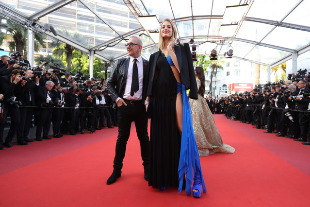 """French fashion designer Jean- Paul Gaultier and guest arrive on May 22, 2017 for the screening of the film """"The Killing of a Sacred Deer"""" at the 70 th edition of the Cannes Film Festival in Cannes, southern France. (Photo by Valery Hache/AFP Photo)"""