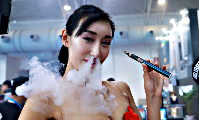 This picture taken on July 23, 2015 shows a sales staff exhaling vapour while demonstrating an electronic cigarette product at the Beijing International Vapor Distribution Alliance Expo, or the Vape China Expo, at the China International Exhibition Center in Beijing. (Photo by AFP Photo)