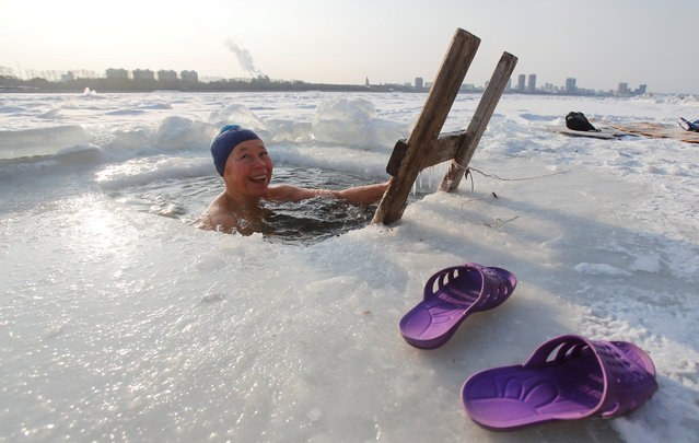 A woman takes a dip in icy water, with the buildings of Chinese border city Heihe seen in the background across the frozen Amur River, in Blagoveshchensk, in Amur region, Russia, December 1, 2019. (Photo by Maxim Shemetov/Reuters)