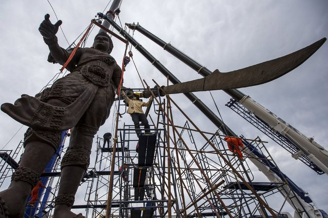 Labourers remove scaffolding from giant bronze statue of former King Ram Khamhaeng at Ratchapakdi Park in Hua Hin, Prachuap Khiri Khan province, Thailand, July 27, 2015. The park is being constructed by the Thai army to honour past Thai monarchs and is situated on an army compound near the Klai Kangwon Palace. The project is estimated to cost about 700 million baht ($20,073,991), according to local media. (Photo by Athit Perawongmetha/Reuters)