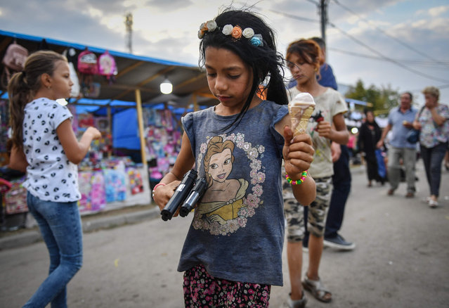 A girl holds toy guns and icecream during the annual Autumn fair on The Day of the Cross in Tandarei city, southern Romania on September 14, 2019. (Photo by Daniel Mihailescu/AFP Photo)