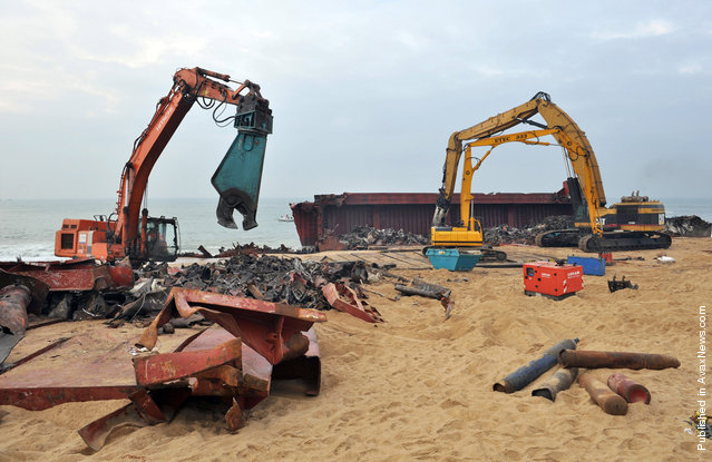 Cranes tear apart and remove scrap metal from the hull of the TK Bremen on January 19, 2012