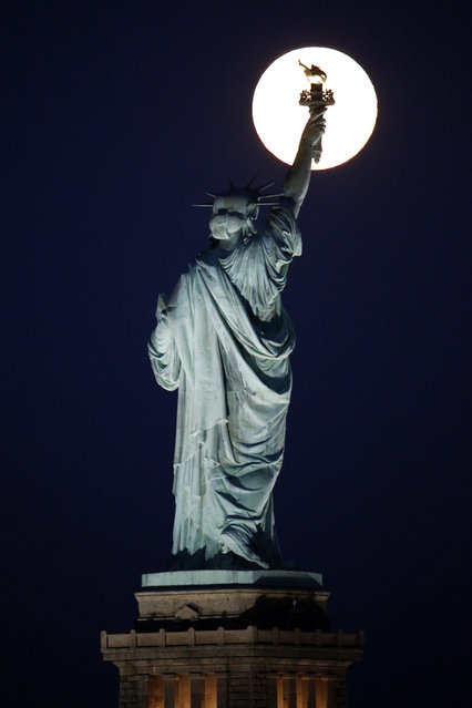 A blue moon rises behind the torch of the Statue of Liberty seen from Liberty State Park in Jersey City, N.J., Friday, July 31, 2015. (Photo by Julio Cortez/AP Photo)