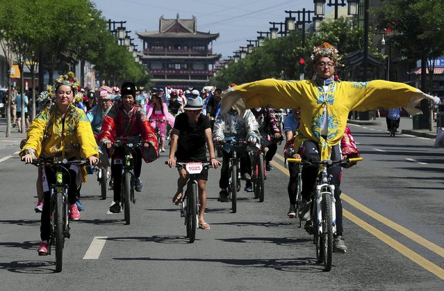 A man in traditional Chinese emperor costume (R) gestures as he and other participants ride their bicycles along a street, during a cycling event in Datong, Shanxi province, China, August 2, 2015. The event, requiring participants to wear Chinese traditional clothing and tour on their bikes around the city, is part of an annual international cycling gathering which will be held from August 1 to 3, local media reported. (Photo by Reuters/China Daily)