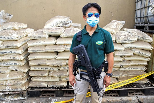 An agent of the Philippine Drug Enforcement Agency stands guard in front of chemicals used in the productions of methamphetamine hydrochloride, or Shabu, during the destructions of chemicals and other evidence in Valenzuela city, north of Manila, Philippines May 24, 2016. (Photo by Romeo Ranoco/Reuters)