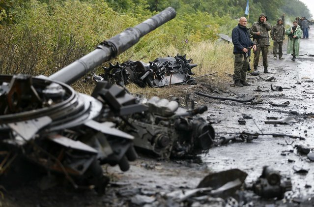 Ukrainian troops stand near destroyed military vehicles just outside the eastern Ukrainian town of Slaviansk July 7, 2014. Ukraine's richest man pleaded with the government on Monday not to bomb Donetsk, a city of a million people where hundreds of heavily armed pro-Russian rebels have vowed to make a stand after losing control of their bastion in the town of Slaviansk. (Photo by Gleb Garanich/Reuters)