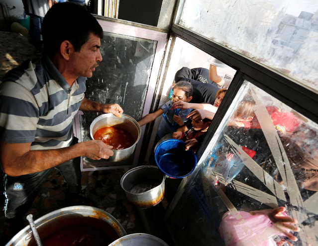 A man distributes free food to displaced people, who fled from Islamic State violence, and the needy during the fasting month of Ramadan at a restaurant in Baghdad, Iraq, June 22, 2016. (Photo by Ahmed Saad/Reuters)