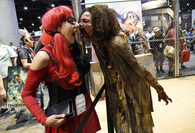 """Judy Hawkins, left, of San Diego, Calif., reacts as a zombie character approaches her at the """"Walking Dead"""" exhibit on the convention show floor during Preview Night of the 2017 Comic-Con International on Wednesday, July 19, 2017, in San Diego, Calif. (Photo by Chris Pizzello/Invision/AP Photo)"""