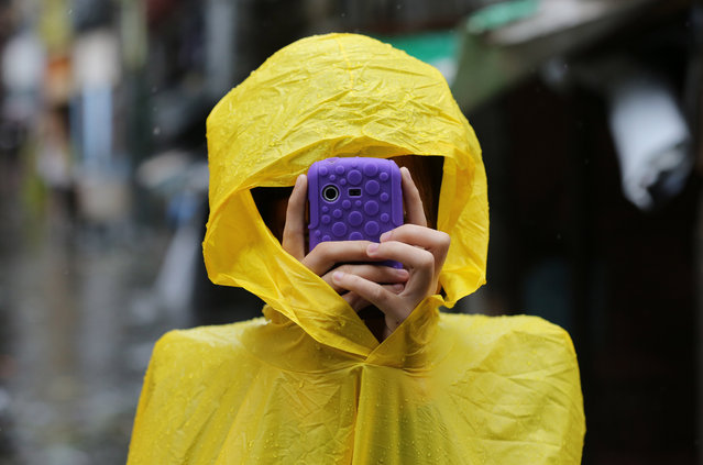 A Filipino resident takes pictures using her smartphone outside a flooded village as Typhoon Rammasun batters suburban Quezon city, north of Manila,  Philippines on Wednesday, July 16, 2014. Typhoon Rammasun knocked out power in many areas but it spared the Philippine capital, Manila, and densely-populated northern provinces from being directly battered Wednesday when its fierce wind shifted slightly away, officials said. (Photo by Aaron Favila/AP Photo)