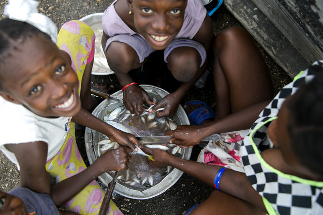 In this December 3, 2019 photo, children help their mother by preparing fish to fry and sell at the Cite Soleil slum of Port-au-Prince, Haiti. A growing number of families across Haiti can't afford to buy enough food since protests began in Sept., with barricades preventing the flow of goods between the capital and the rest of the country. (Photo by Dieu Nalio Chery/AP Photo)