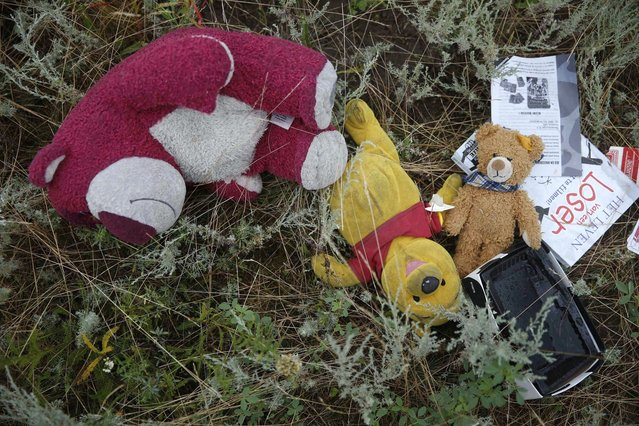 Passengers' belongings are pictured at the crash site of Malaysia Airlines flight MH17 before a visit by Organisation for Security and Cooperation in Europe (OSCE) monitors, near the settlement of Grabovo in the Donetsk region, July 18, 2014. OSCE monitors were not able to secure an access corridor on Friday to the site where the Malaysian airliner crashed in eastern Ukraine, the OSCE's chairman said. (Photo by Maxim Zmeyev/Reuters)