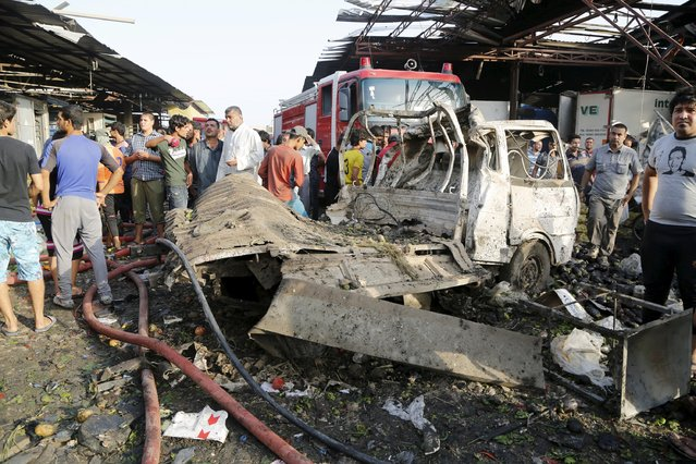 A destroyed vehicle is seen at the site of a truck bomb attack at a crowded market in Baghdad August 13, 2015. (Photo by Wissm Al- Okili/Reuters)
