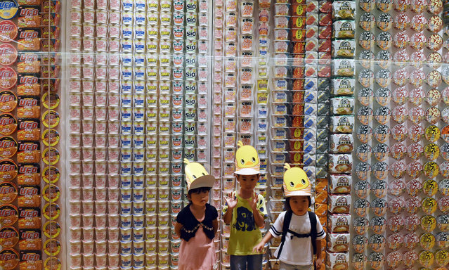 Children pose for a photo in front of a display of instant noodle packages from various countries at the Cup Noodle Museum in Yokohama, suburban Tokyo on August 13, 2015. The museum has had some four million visitors since opening its doors in 2011. (Photo by Yoshikazu Tsuno/AFP Photo)