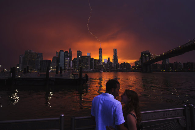 Joseph Rojas and Abigail Zolotarsky embrace as lightning strikes One World Trade Center in Manhattan during sunset after a summer storm in New York July 2, 2014. (Photo by Lucas Jackson/Reuters)