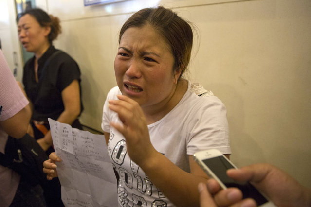 Wang Baoxia talks to a journalist about her missing brother Wang Quan who was at the scene of an explosion in northeastern China's Tianjin municipality, Saturday, August 15, 2015. Angry family members of firefighters missing in the explosions that rocked the Chinese port city of Tianjin stormed a government news conference on Saturday, demanding information on their loved ones. (Photo by Ng Han Guan/AP Photo)
