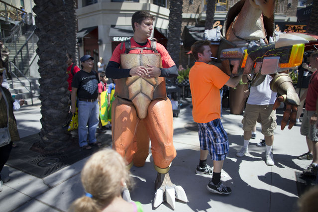 Chris Rose puts on his suit, a new comic book character named Rexodus during Comic-Con Thursday, July 24, 2014, in San Diego. (Photo by AP Photo)