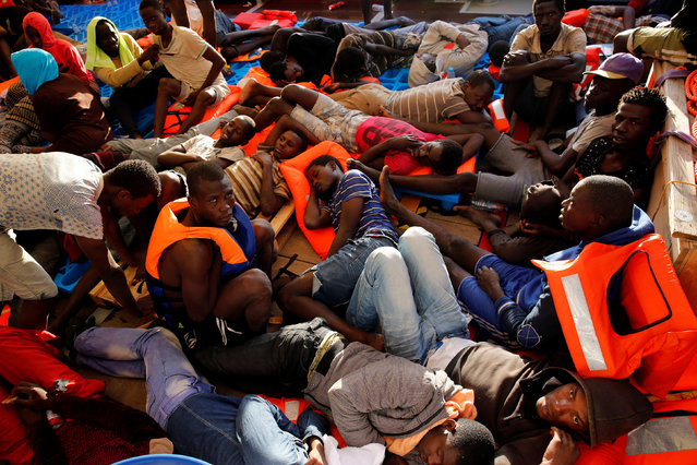 Migrants rest on the deck of the Migrant Offshore Aid Station (MOAS) ship Topaz Responder after being rescued around 20 nautical miles off the coast of Libya, June 23, 2016. (Photo by Darrin Zammit Lupi/Reuters)