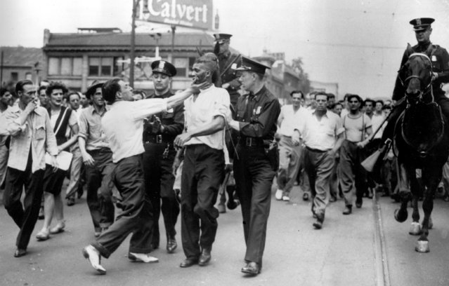 Sam Mitchell, a 46-year-old black janitor, is assaulted by George Miller as police escort Mitchell after he was shot in the stomach during rioting in the edge of the downtown area of Detroit, Mich., June 21, 1943. U.S. troops were called in when police were unable to stop the fighting. (Photo by AP Photo)