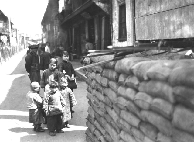 1927: Chinese children, watched over by some adults, study an artillery post. This temporary post is used to house British troops defending Shanghai