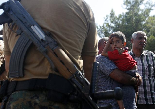 A Macedonian police officer blocks migrants at no-man's land between Greece and Macedonia near the southern Macedonian town of Gevgelija, Thursday, August 20, 2015. (Photo by Darko Vojinovic/AP Photo)