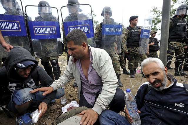 Macedonian policemen stand guard in front of migrants at the Greek-Macedonian border, August 21, 2015. (Photo by Alexandros Avramidis/Reuters)