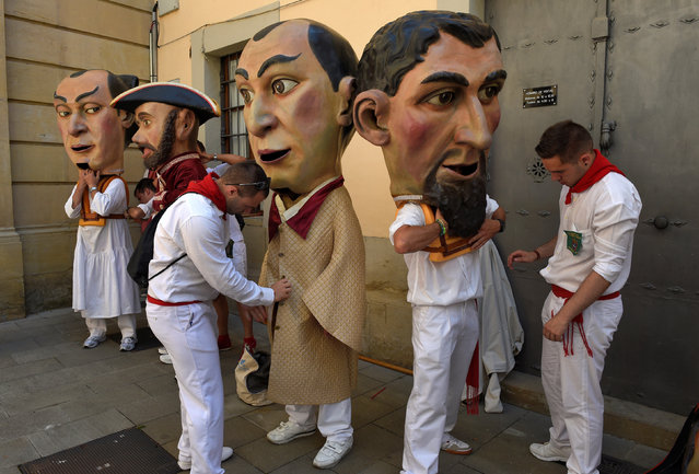 """Assistants help """"Kilikis"""", Big Heads, to dress at the San Fermin festival in Pamplona, northern Spain July 8, 2016. (Photo by Eloy Alonso/Reuters)"""