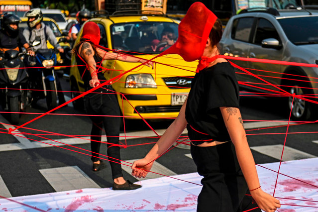 Colombian activists perform during a protest against violence towards women, on a street in Medellin, Colombia, on March 6, 2020. (Photo by Joaquín Sarmiento/AFP Photo)