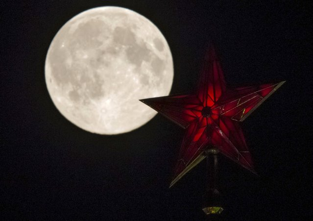 The supermoon rises over the stars of Moscow's Kremlin towers in Moscow August 10, 2014. (Photo by Maxim Shemetov/Reuters)