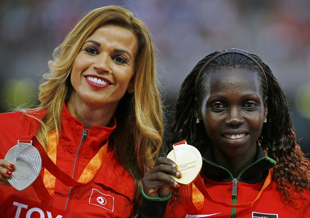 Hyvin Kiyeng Jepkemoi of Kenya, gold medal, (R) and Habiba Ghribi of Tunisia, silver medal pose on the podium after the women's 3000 metres steeplechase event during the 15th IAAF World Championships at the National Stadium in Beijing, China, August 27, 2015. (Photo by Damir Sagolj/Reuters)