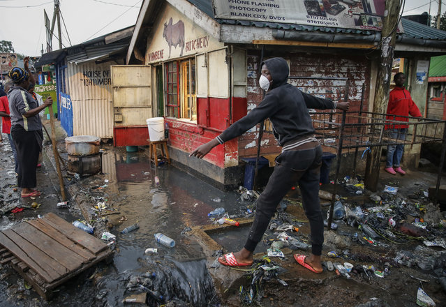 A boy wears a mask as a preventative measure against the spread of the new coronavirus, as he navigates a flood of water mixed with garbage following heavy rains, in the Kibera slum, or informal settlement, of Nairobi, Kenya, Thursday, March 26, 2020. Many slum residents say staying at home or social-distancing is impossible for those who live hand to mouth and receive daily wages for informal work, as is maintaining sanitation in densely populated areas where a pit latrine can be shared by over 50 people. (Photo by Brian Inganga/AP Photo)