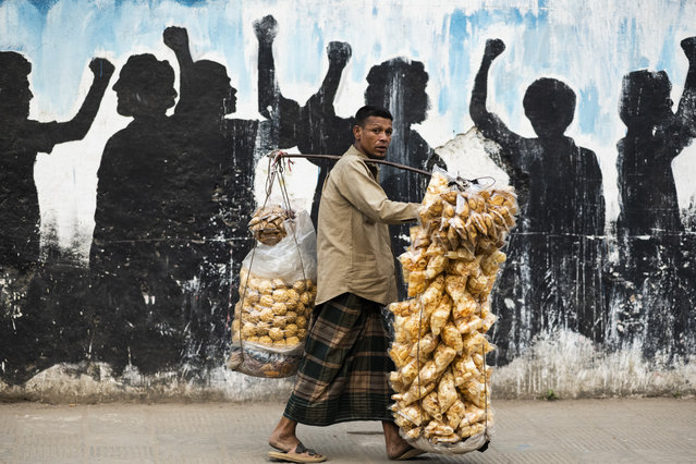 A traditional snacks vendor looks for customers along a street in Dhaka, Bangladesh on March 2, 2020. (Photo by Jewel Samad/AFP Photo)