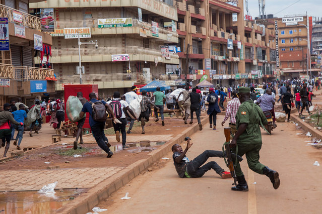 A police officer chases street vendors in Kampala, Uganda, on March 26, 2020, after  Ugandan President Yoweri Museveni directed the public to stay home for 32 days starting March 22, 2020 to curb the spread of the COVID-19 coronavirus. Ugandan authorities have identified 14 confirmed cases of the COVID-19 coronavirus in the country. All borders have been closed except for limited goods and authorised emergency flights. (Photo by Badru Katumba/AFP Photo)