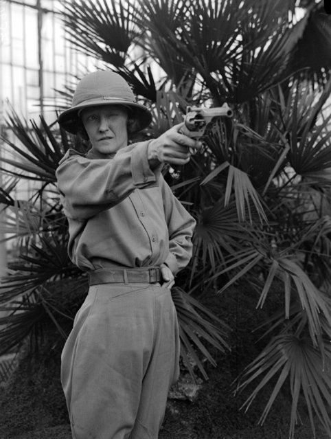 Dressed for deepest Africa and wearing a solar topee, Mrs. T. G. Glover takes aim with her revolver in the Botanic Gardens at Kew, London. 2nd February 1931. (Photo by Fox Photos)