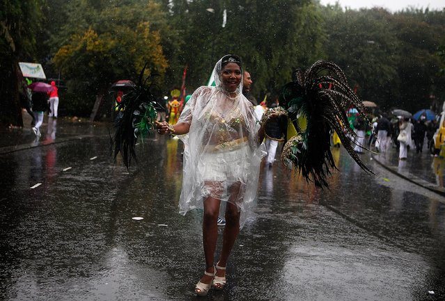 A performer dances through heavy rain during the Notting Hill Carnival on August 25th, 2014 in London, England. Despite the bad weather over 1 million visitors are expected to attend the two-day event which is the largest of its kind in Europe. The event has taken place on the West London streets every August Bank Holiday weekend since 1964. (Photo by Mary Turner/Getty Images)