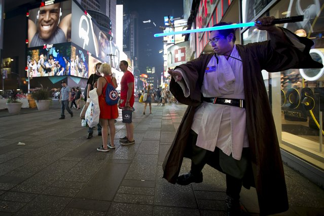 "Star Wars fan Mike Deguzman practices with a toy lightsaber after purchasing some new toys that went on sale at midnight in advance of the film ""Star Wars: The Force Awakens"" in Times Square in the Manhattan borough of New York, September 4, 2015. (Photo by Carlo Allegri/Reuters)"