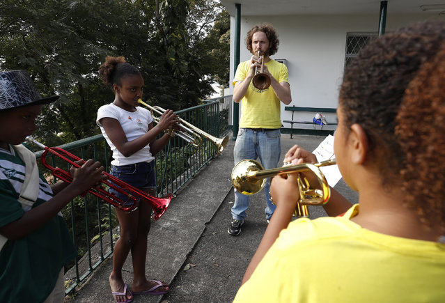 British man Tom Ashe, 36, a professional trumpet player, who founded Favela Brass plays trumpet with favela children during band rehearsals in Pereira da Silva favela, in Rio de Janeiro, Brazil, 01 August 2016. Tom's love of Brazilian live music bought him to Rio, Favela Brass will play every day in Rio neighborhoods during the Rio 2016 Olympic Games. Tom who lives in the same favela as the children started with one student in 2014 and now has 36 students, aged between 5 to 15. (Photo by Barbara Walton/EPA)