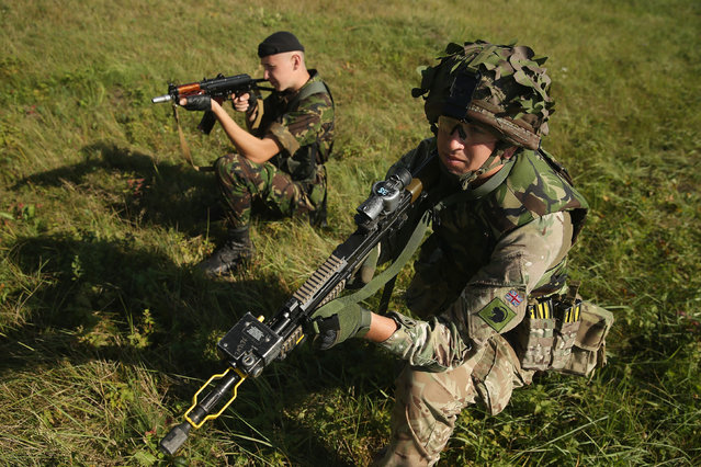 "A Ukrainian soldier (L) and a member of the British Light Dragoons practice anti-IED (improvised explosive device) location and removal training on the second day of the ""Rapid Trident"" NATO military exercises on September 16, 2014 near Yavorov, Ukraine. (Photo by Sean Gallup/Getty Images)"