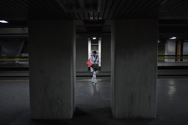A commuter wearing a mask as a precaution against the new coronavirus, waits for the subway in Caracas, Venezuela, Sunday, April 12, 2020, during a government-imposed quarantine to help stop the spread of the new coronavirus. (Photo by Matias Delacroix/AP Photo)