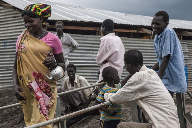 A group of people gather at a small bridge at the Protection of Civilians (POC) site at the United Nations Mission in South Sudan (UNMISS) compound in Malakal, South Sudan on Wednesday, July 13, 2016. (Photo by Jane Hahn/The Washington Post)