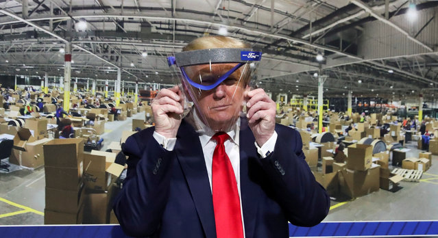 U.S. President Donald Trump holds up a protective face shield during a tour of the Ford Rawsonville Components Plant that is manufacturing ventilators, masks and other medical supplies during the coronavirus disease (COVID-19) pandemic in Ypsilanti, Michigan, U.S., May 21, 2020. (Photo by Leah Millis/Reuters)
