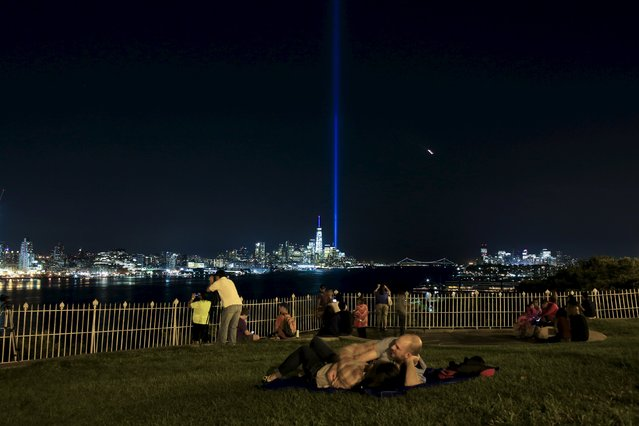 The Tribute in Light is illuminated next to the One World Trade Center while people enjoy the view along the Hudson River during events marking the 14th anniversary of the 9/11 attacks on the World Trade Center in New York September 11, 2015. (Photo by Eduardo Munoz/Reuters)