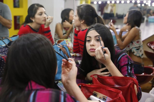 Girls practice makeup techniques during a class at a modelling academy in Caracas September 20, 2014. (Photo by Carlos Garcia Rawlins/Reuters)