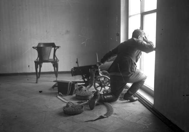 In this photo taken in October 1917, provided by Russian State Documentary Film and Photo Archive, a machine gunner looks through a window at his position near the Kremlin in Moscow, Russia. The 1917 Bolshevik Revolution was long before the digital revolution allowed anyone to instantly document events. But the clumsy cameras of the time still caught some images that capture the period's drama. (Photo by Russian State Documentary Film and Photo Archive via AP Photo)