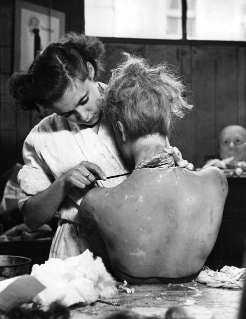 An employee of Gems Ltd, a firm based in a disused chapel off Portobello Road, London, fixes the wax head of a model onto its body. The firm makes wax and composition models, including likenesses of criminals, politicians and royalty, as well as mannequins to display fashion. November 1950. (Photo by John Chillingworth/Picture Post)